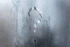 有雾的结露玻璃窗自然表面上的模糊的问号 免版税库存照片