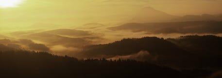 从有雾的背景和小山增加的砂岩峰顶,雾是桔子由于太阳光芒。 免版税库存图片