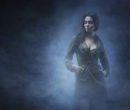 有雾的背景的一名年轻和性感的深色的妇女 库存图片