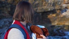 有震动她的胳膊的背包的美丽的年轻母亲睡觉的男婴 影视素材