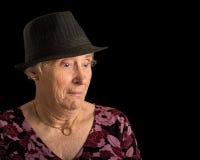 有震惊神色的资深夫人在她的佩带浅顶软呢帽的面孔 库存照片