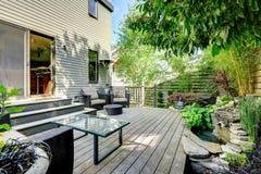 有露台区域的美妙地被设计的后院 免版税库存照片