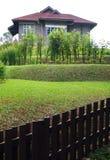 有露台的庭院和篱芭的老石房子 库存图片