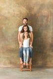 有青少年的女儿和丈夫的怀孕的母亲 家庭在棕色背景的演播室画象 库存照片
