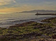 有青苔的帕尔马海岸线在岩石、山、光烽火台和美丽的天空,马略卡,西班牙 免版税图库摄影
