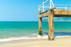 有青苔的老码头在有波浪的海洋在海滩在阳光下 免版税库存照片