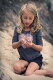 有青蛙的女孩在海滩 免版税库存图片