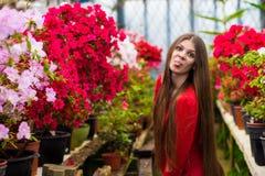 有非常长的头发的相当微笑的少妇在一件红色女衬衫 免版税库存照片