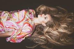 有非常长的金发的少妇躺下演播室射击 免版税库存图片