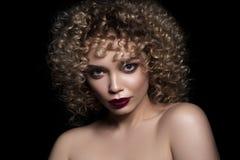 有非洲的卷毛发型的逗人喜爱的白种人妇女在黑暗的背景 她佩带黑暗的晚上或指挥台用红色染睫毛油组成 库存图片