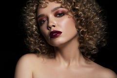 有非洲的卷毛发型的逗人喜爱的白种人妇女在黑暗的背景 她佩带黑暗的晚上或指挥台用红色染睫毛油组成 免版税库存照片
