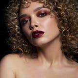 有非洲的卷毛发型的逗人喜爱的白种人妇女在黑暗的背景 她佩带黑暗的晚上或指挥台用红色染睫毛油组成 图库摄影