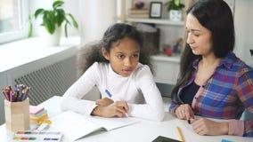 有非洲的发型的可爱的女孩坐在桌上并且与白种人老师谈话 影视素材