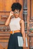 有非洲的发型的年轻非裔美国人的大学生,眼睛玻璃,佩带的无袖的淡色上面,黑裙子,传送带, 库存图片