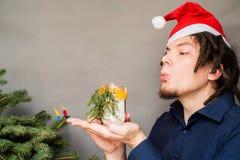 有非洲的发型的白种人人和拿着一种手工制造蜡烛工艺的圣诞老人帽子 免版税图库摄影