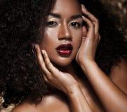 有非洲的头发的年轻典雅的非裔美国人的妇女 魅力构成 金黄的背景 免版税库存照片