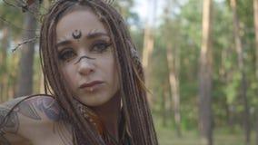 有非洲辫子和纹身花刺的可爱的树精或森林神仙在一套美丽的服装的身体跳舞 ?? 影视素材