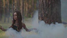 有非洲辫子和纹身花刺的可爱的树精或森林神仙在美丽的服装的身体跳舞在云彩  股票视频