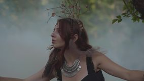 有非洲辫子和纹身花刺的可爱的树精或森林神仙在美丽的服装的身体跳舞在云彩  股票录像