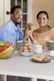 有非洲裔美国人的早餐的夫妇坐 库存图片