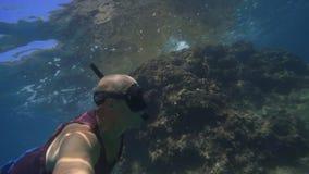 有面具和废气管的一个人和在水下的自由潜水 影视素材