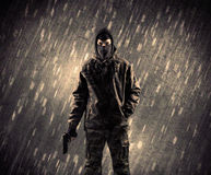 有面具的武装的恐怖分子人在多雨背景 免版税图库摄影