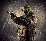 有面具的武装的恐怖分子人在多雨背景 库存图片