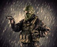 有面具的武装的恐怖分子人在多雨背景 免版税库存图片