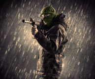 有面具的武装的恐怖分子人在多雨背景 免版税库存照片