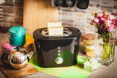 有面包切片的多士炉在厨房用桌上 免版税库存照片