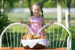 有面包篮子的一个孩子在长凳的 免版税图库摄影
