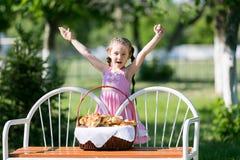 有面包篮子的一个孩子在长凳的 免版税库存图片