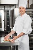 有面团盘的男性厨师由柜台 图库摄影