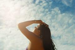 有面孔的女孩被转动往太阳 免版税库存图片