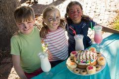 有面孔的愉快的朋友由食物绘坐并且喝在桌上 库存照片