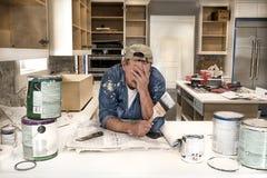 有面孔的被用尽的和疲乏的画家在拿着湿画笔的手上在有油漆罐头的杂乱家庭厨房里到处 免版税库存图片