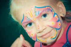 有面孔绘画的俏丽的女孩孩子 组成 免版税库存图片