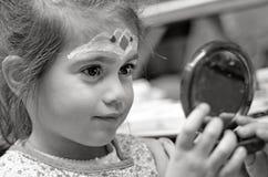 有面孔绘画的小女孩看镜子 图库摄影