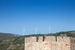有面对一座老城堡的风轮机和风车的罗马尼亚风力场位于多瑙河的塞尔维亚边 免版税库存照片