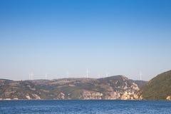 有面对一座老城堡的风轮机和风车的罗马尼亚风力场位于多瑙河的塞尔维亚边 图库摄影