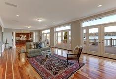 有面对湖的玻璃门墙壁的豪华宽敞家庭娱乐室  图库摄影