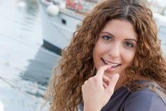 有面对照相机的卷发的俏丽的妇女 免版税库存图片