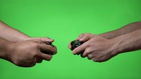 有面对的无线控制器的两个紧张的年轻录影游戏玩家在绿色屏幕背景的一次比赛- 股票视频