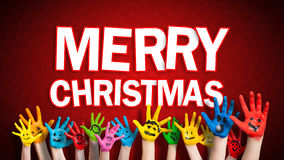 有面带笑容的被绘的儿童手与圣诞快乐消息 库存照片