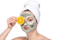 有面部面具和桔子的美丽的妇女 免版税库存照片