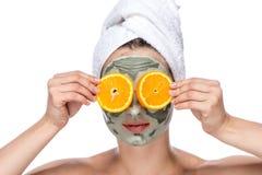 有面部面具和桔子的美丽的妇女 库存图片