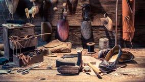 有鞋子、鞋带和工具的补鞋匠车间 免版税库存照片