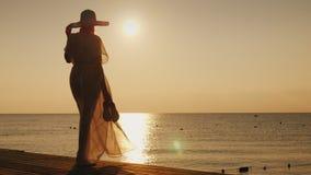 有鞋子的一名浪漫妇女在她的手上在码头站立,遇见黎明 梦想和旅行概念 免版税库存图片