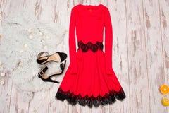 有鞋带、黑鞋子和一张仿制毛皮的红色礼服在木背景,时兴的概念,顶视图 免版税图库摄影
