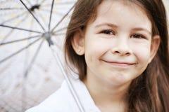 有鞋带伞的俏丽的女孩在白色衣服 免版税图库摄影